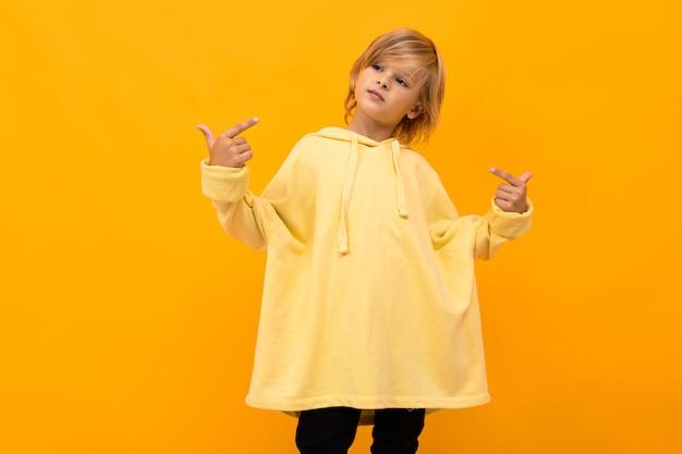 Cooler blonder junge mit einem panama in einem hellen kapuzenpulli mit brille, die auf gelbem studio aufwirft