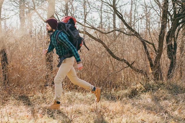 Cooler hipster-mann, der mit rucksack im herbstwald mit kariertem hemd und hut reist, aktiver touristenlauf, natur in der kalten jahreszeit erforschend