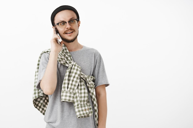 Cooler hipster-typ, der einladende freunde anruft, kommt vorbei und greift nach dem bären, der das smartphone in der nähe des ohrs hält, während er am telefon spricht und mit lässigem normalem ausdruck in schwarzer mütze und brille nach rechts schaut