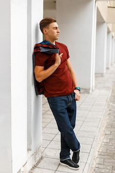 Cooler hübscher junger mann im trendigen roten t-shirt in einem modischen karierten hemd in den blauen jeans in den turnschuhen, die auf der straße nahe einem weißen weinlesegebäude aufwerfen
