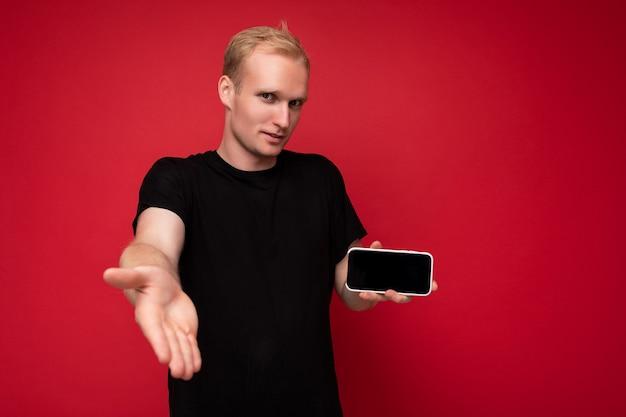Cooler hübscher positiver blonder junger mann, der ein schwarzes t-shirt trägt, das isoliert auf rotem hintergrund steht