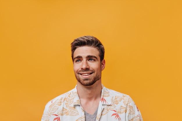 Cooler junger kerl mit bart und blauen augen in leicht bedrucktem sommerhemd, der wegschaut und auf orangefarbener isolierter wand lächelt