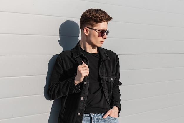 Cooler junger mann des frischen porträts mit frisur in modischer schwarzer jeansjacke in stilvoller sonnenbrille