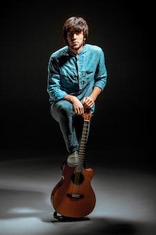 Cooler kerl, der mit gitarre auf dunkelheit steht