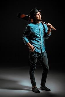 Cooler kerl, der mit gitarre auf dunklem raum steht