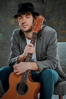 Cooler kerl, der mit gitarre auf grau sitzt