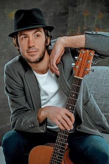 Cooler kerl, der mit gitarre auf grauzone sitzt