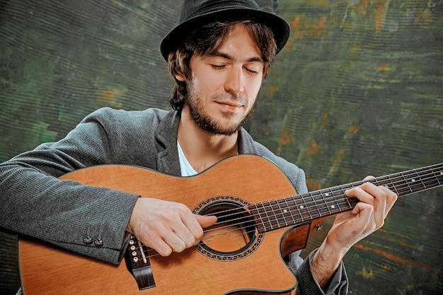 Cooler kerl mit hut, der gitarre auf grau spielt