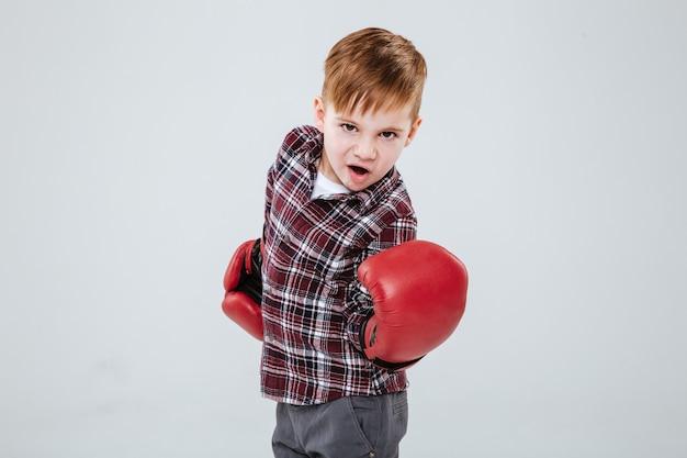 Cooler kleiner junge in roten boxhandschuhen, der über weißer wand steht und trainiert