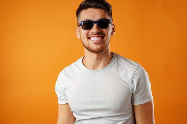 Cooler lächelnder kerl in der schwarzen sonnenbrille und im weißen hemd