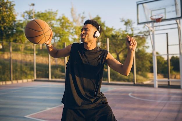 Cooler lächelnder schwarzer mann, der sport treibt, basketball bei sonnenaufgang spielt, musik über kopfhörer hört, aktiver lebensstil, sommermorgen