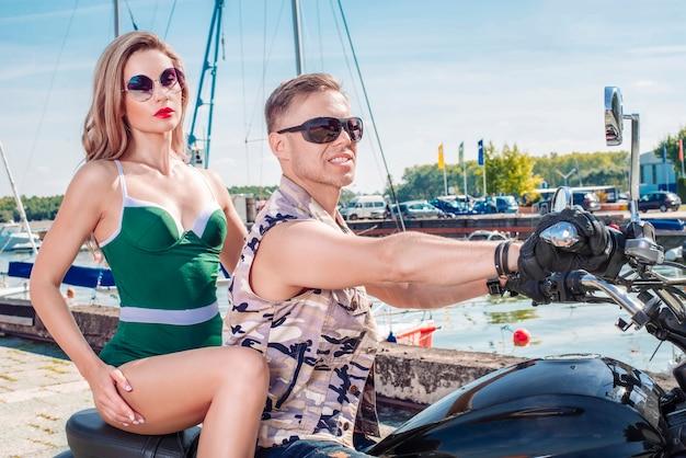 Cooler mann und eine atemberaubende stylische blondine in einem grünen badeanzug, die auf einem motorrad fährt. familie, tourismus, liebeskonzept. gemischte medien