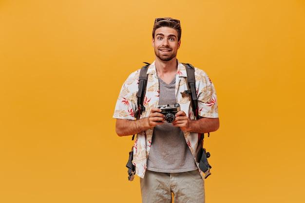 Cooler modischer typ mit ingwerbart im sommerhemd, grauem t-shirt und coolen sonnenbrillen mit kamera an isolierter wand