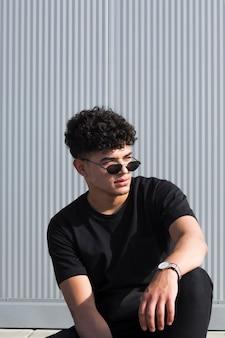 Cooler schwarzer typ mit lockigem haar in sonnenbrille