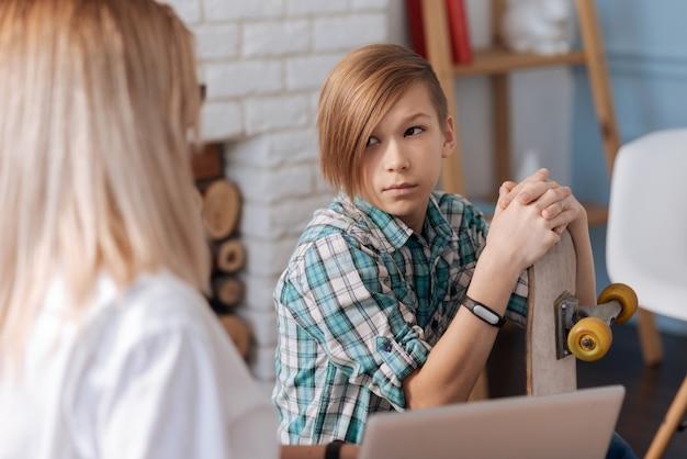 Cooler teenager mit stilvollem haarschnitt, der fitness-armband auf der rechten hand trägt und seine beiden hände auf skateboard legt, während er seinen kopf auf frau dreht