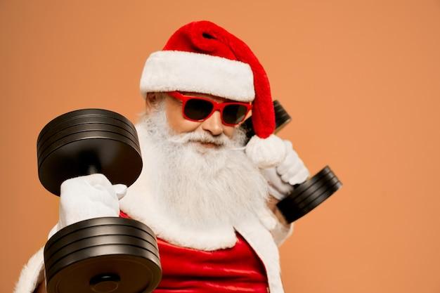 Cooler weihnachtsmann mit echtem barttraining mit zwei hanteln