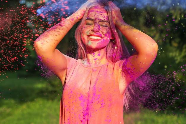 Cooles blondes model mit langen haaren bedeckte lila trockene farbe, die das holi-festival feierte