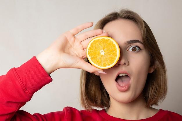 Cooles brunettemädchen, das mit einer halben orange aufwirft und ein auge bedeckt, gegen weiße wand. platz für text