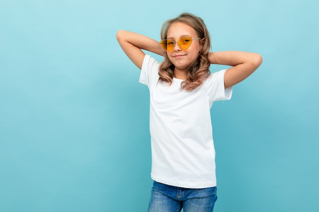 Cooles kaukasisches teenager-mädchen im weißen t-shirt, gelbe brille lächelt und zeigt sich isoliert auf blauem hintergrund