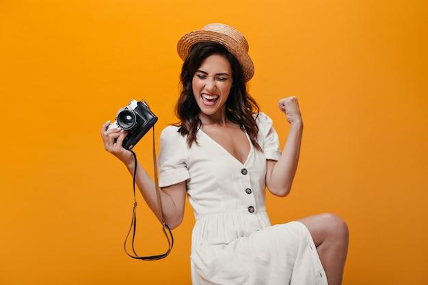 Cooles mädchen im weißen kleid, das glücklich auf orange hintergrund aufwirft und retro-kamera hält