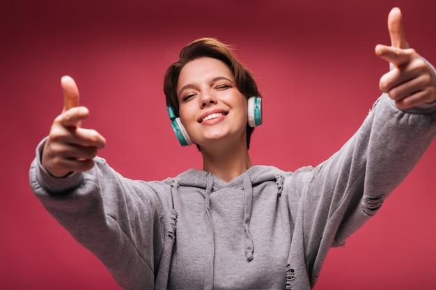 Cooles mädchen in den kopfhörern, die zwinkern und auf kamera auf rosa hintergrund zeigen. junge frau im kapuzenpulli hört musik auf isoliertem hintergrund