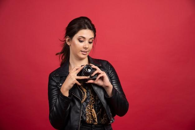 Cooles mädchen in der schwarzen lederjacke, die ihre professionelle kamera hält und gute fotos macht.