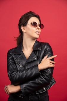 Cooles mädchen in der schwarzen lederjacke, die in der schwarzen sonnenbrille aufwirft.