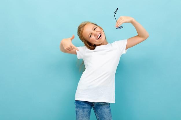 Cooles mädchen in einem weißen t-shirt mit modell auf hellblau