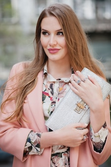 Cooles porträt der attraktiven stilvollen lächelnden frau, die stadtstraße im rosa mantelfrühlingsmodetrend hält geldbörse geht