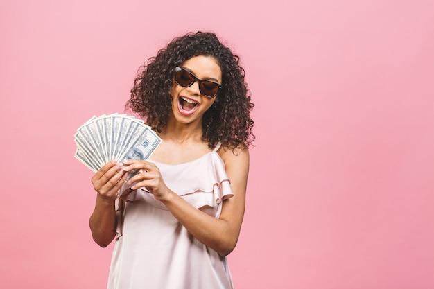 Cooles reiches mädchen! geldgewinner! überraschte schöne afroamerikanerfrau im kleid, das geld in der sonnenbrille hält, die gegen rosa hintergrund lokalisiert wird.