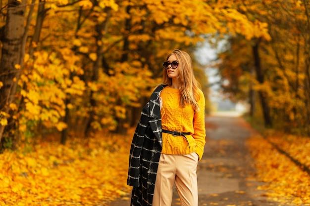 Cooles, stylisches junges model-mädchen mit modischer runder sonnenbrille in einem modischen hut mit einem stylischen sommeroberteil, hosen und schuhen, die mit sonnenlicht auf der straße posieren