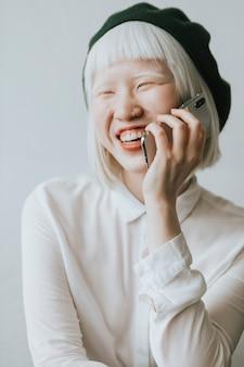 Cooles und stylisches albino-mädchen, das an ihrem telefon spricht