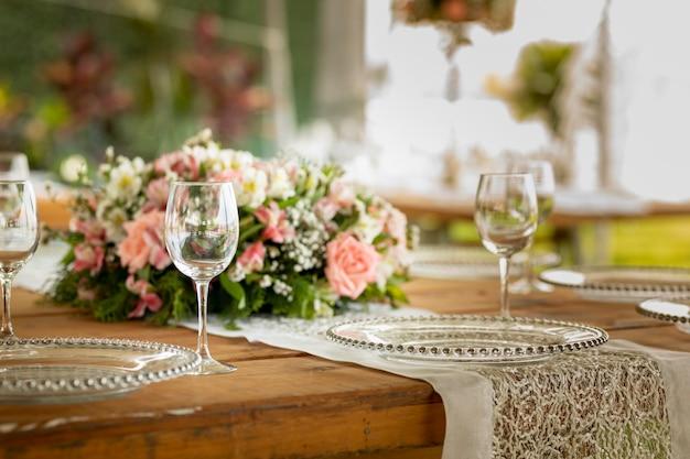 Copa de cristal sobre una mesa con arreglos florales