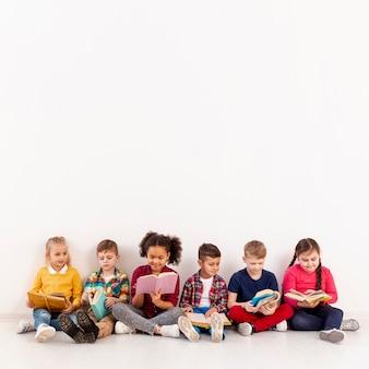 Copy-space-gruppe von kindern auf dem boden lesen