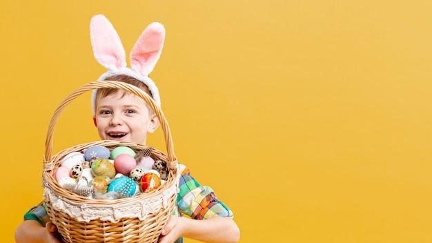Copy-space-junge mit korb voller bemalter eier