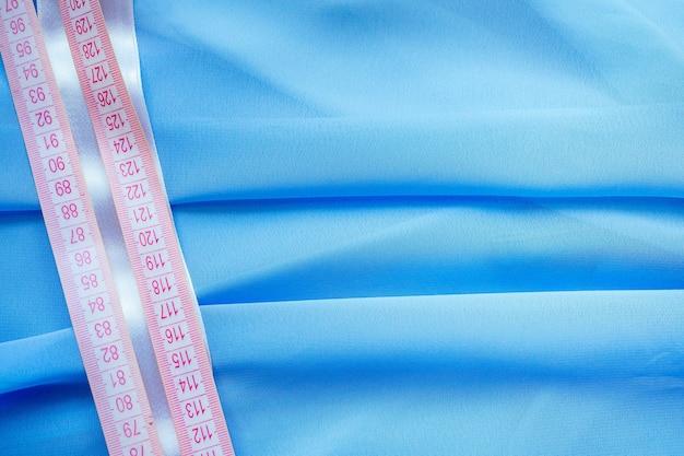 Copyspace close-up blauer chiffon, fäden und maßband schneiderin (schneiderin) designer-hochzeitskleid näht perlen zum spitzen auf blauem hintergrund im studio