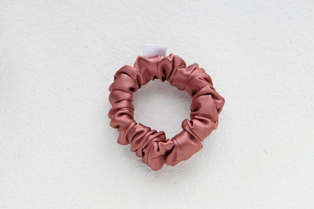 Coral-pink haarschmuck - seidenrosa scrunchy isoliert auf weißem hintergrund. flache frisurenwerkzeuge und accessoires für damen - bunte haargummis, textilelastische haarbänder