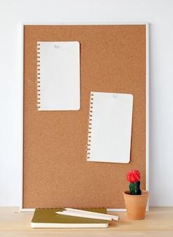 Corkboard mit Notiz und Kaktus des leeren Papiers