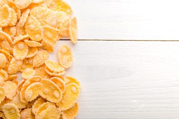 Corn flakes auf weißem hölzernem hintergrund