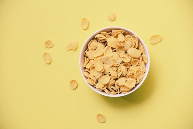 Corn-flakes frühstücken in der schüssel auf gelbem hintergrund für gesundes lebensmittel des getreides