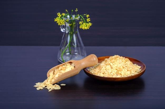 Corn-flakes im hölzernen löffel auf einem dunklen holz