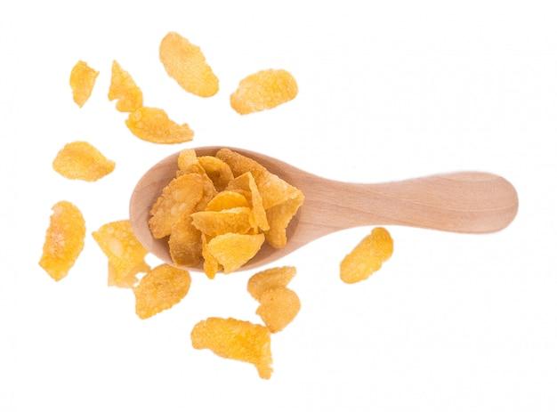 Corn flakes im hölzernen löffel lokalisiert