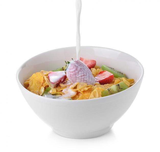 Corn flakes mit milch und frischer frucht auf weiß