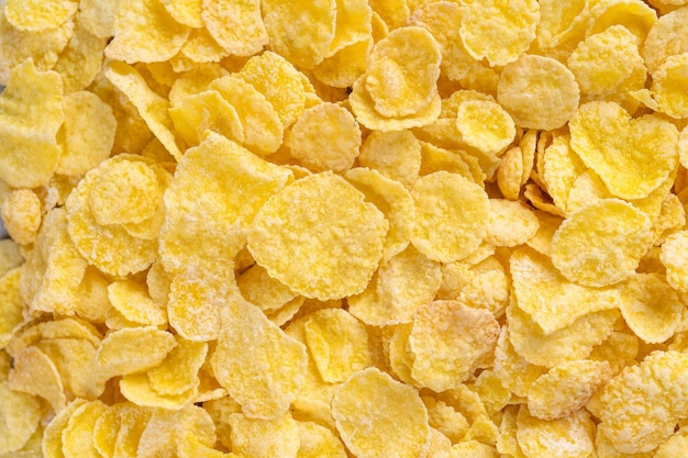 Corn flakes schüssel süßigkeiten auf grauem zement hintergrund, draufsicht flach layout design, frisches und gesundes frühstückskonzept.