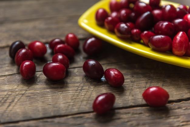 Cornelian cherry hartriegel essbare früchte in schüssel auf holztisch