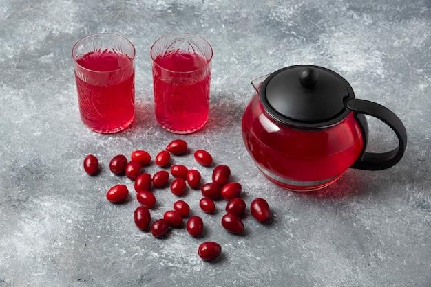 Cornels und roter saft in gläsern und wasserkocher.
