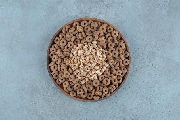 Cornflakes in der holzplatte, auf blauem hintergrund. foto in hoher qualität