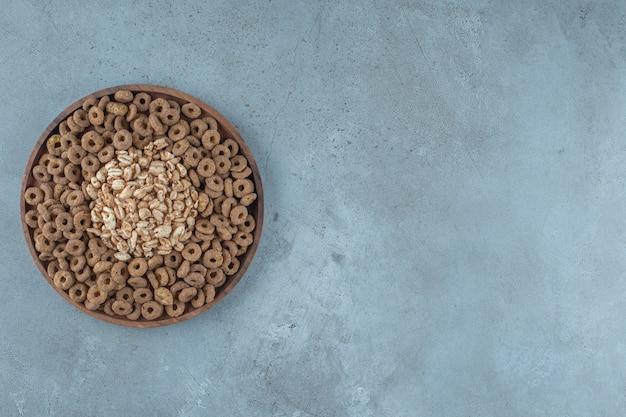 Cornflakes in der holzplatte, auf blauem hintergrund.