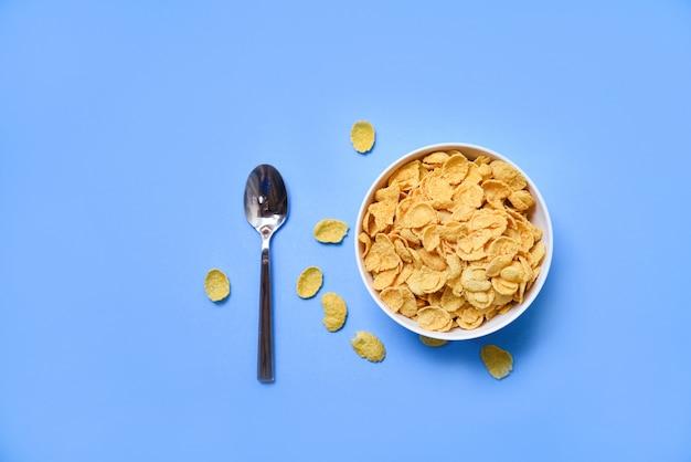 Cornflakes in der schüssel auf blau und löffel für gesundes lebensmittel des getreides