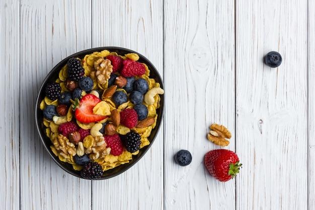 Cornflakes in der schüssel mit beeren und nüssen auf weißem hölzernem hintergrund. draufsicht auf gesundes frühstück.